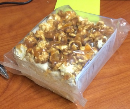 This is a double-marshmallow rice krispy treat covered in CARAMEL CORN, guys,  _Caramel corn._